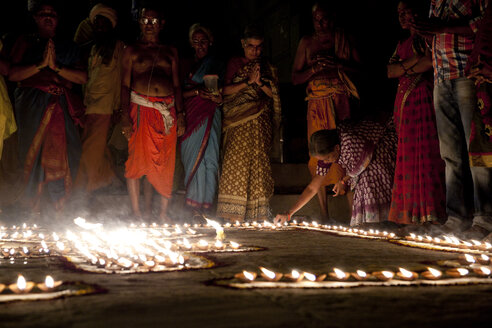 India, Uttar Pradesh, Varanasi, Maha Shivaratri, a woman lighting a oil lamp - JBA000050