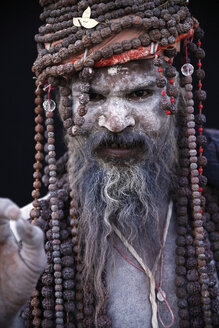 India, Uttar Pradesh, Varanasi, portrait of Sadhu with many pearl necklets on head and shoulders - JBA000058