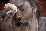 India, Uttar Pradesh, Varanasi, portrait of Sadhu powdering himself with ash - JBA000064