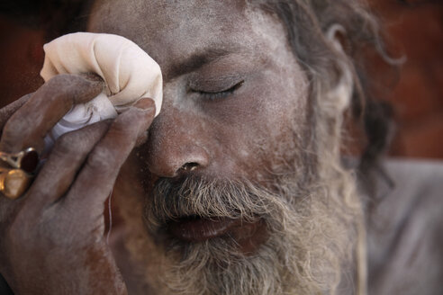 India, Uttar Pradesh, Varanasi, portrait of Sadhu powdering himself with ash - JBA000064