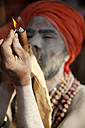 India, Uttar Pradesh, Varanasi, portrait of Sadhu lighting chillum pipe - JBA000067