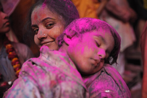 India, Uttar Pradesh, Vrindavan, Holi, spring festival, festival of colours, mother with sleeping child - JBA000039