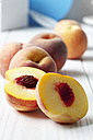 Whole and sliced peaches (Prunus persica) on white wooden table - CSF020782