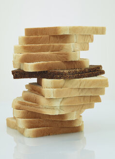 Single slice of black bread in a stack of toast bread - AKF000317