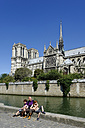 France, Ile-de-France, Paris, Notre Dame de Paris, with Seine river, father and children sitting at riverside - LB000536