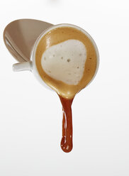 White coffee dropping out of coffee cup in front of white background - AKF000323