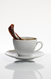 Black coffee splashing out of white coffee cup in front of white background - AKF000305