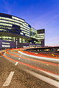 Germany, Baden-Wuerttemberg, Stuttgart, office building and light trails on street at twilight - WDF002244