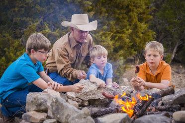 USA, Texas, Father and sons roasting sausages over camp fire - ABAF001202