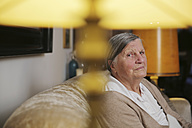 Senior woman sitting on a couch at living room - JATF000662