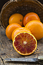Half and whole blood oranges and pocket knife on wooden table - LVF000564