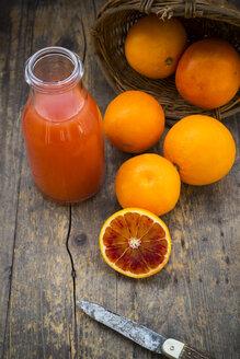 Half and whole blood oranges, bottle of blood orange juice and pocket knife on wooden table - LVF000566
