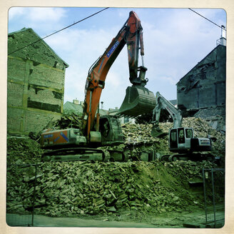 Excavator on pile of rubble of a demolished house, Vienna, Austria - DIS000534