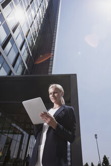 Businesswoman outside office building using tablet pc - CHAF000086