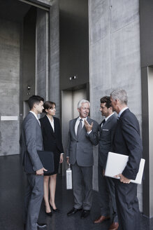 Group of businesspeople discussing at elevator - CHAF000049