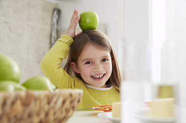 Germany, Munich, Girl sitting at table with green apple - FSF000184