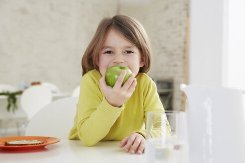 Germany, Munich, Girl sitting at table with green apple - FSF000176