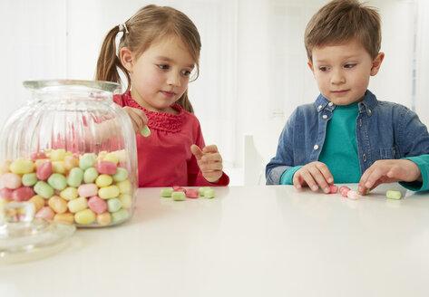Germany, Munich, Boy and girl with candy jar - FSF000159
