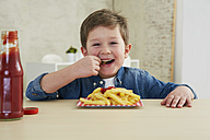 Germany, Munich, Boy eating French fries with ketchup - FSF000197