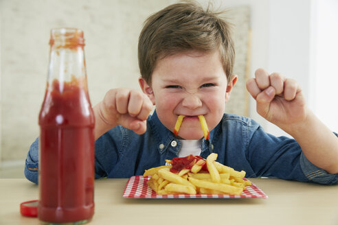 Germany, Munich, Boy eating French fries with ketchup - FSF000196