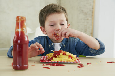 Germany, Munich, Boy eating French fries with ketchup - FSF000194