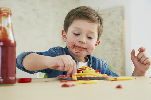 Germany, Munich, Boy eating French fries with ketchup - FSF000191