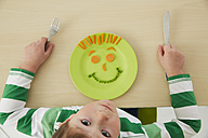 Germany, Munich , Boy eating peas and carrots showing anthropomorphic face - FSF000187