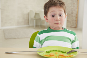 Germany, Munich , Boy eating peas and carrots showing anthropomorphic face - FSF000149