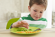 Germany, Munich , Boy eating peas and carrots showing anthropomorphic face - FSF000146