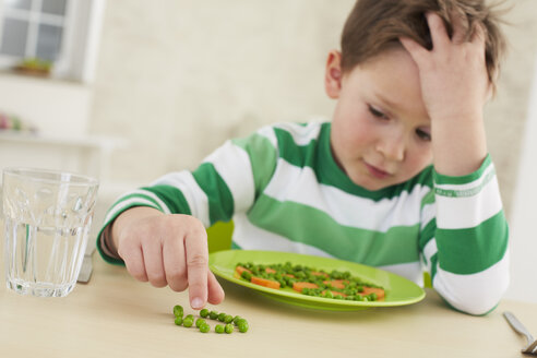 Germany, Munich , Boy doesn't want to eat  peas and carrots - FSF000143