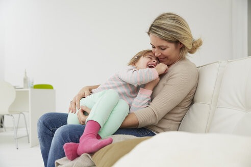 Germany, Munich, Mother and daughter sitting on sofa, cuddling - FSF000132