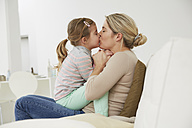 Germany, Munich, Mother and daughter sitting on sofa - FSF000129