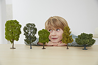Germany, Boy sitting at table with tree models, environmental conservation - FSF000113