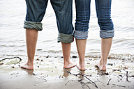 Naked feet of young couple standing in the water of Rhine river - PAF000358