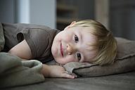 Smiling little girl lying on pillow, portrait - FKF000401