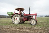 Germany, Rhineland-Palatinate, Neuwied, farmer sowing artificial fertilizer with tractor - PA000365