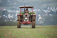 Germany, Rhineland-Palatinate, Neuwied, farmer sowing artificial fertilizer with tractor - PA000374
