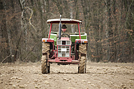 Germany, Rhineland-Palatinate, Neuwied, farmer sowing artificial fertilizer with tractor - PA000378
