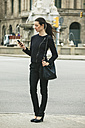 Spain, Catalunya, Barcelona, young black dressed businesswoman looking at her smartphone in front of a street - EBSF000003