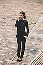 Spain, Catalunya, Barcelona, young black dressed businesswoman telephoning on a square - EBSF000015