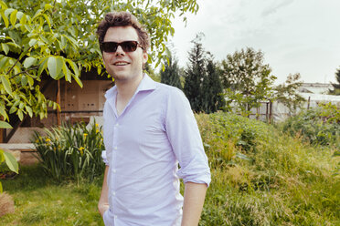 Man wearing sunglasses and standing in his vegetable garden - MFF000878