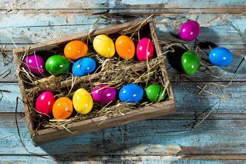 Wooden box of shiny coloured Easter eggs on wooden ground - MAEF007780