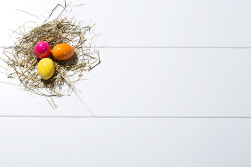 Three coloured Easter eggs and straw on white ground - MAEF007772