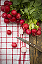 Sliced and whole red radishes and knife on kitchen towel - LVF000601
