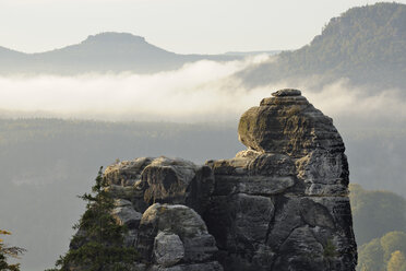 Germany, Saxony, National Park Saxon Switzerland, Elbe Sandstone Mountains, view to rock formation with morning fog in background - RUEF001204