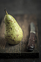 Pear with water trops and knife on chopping board - SBDF000567