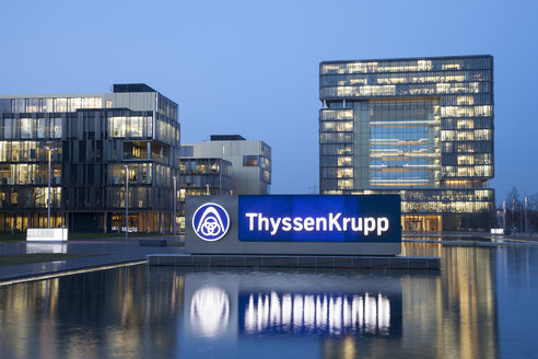 Germany, North Rhine-Westphalia, Essen, Krupp-Guertel, lighted logo in front of headquarter of ThyssenKrupp at evening twilight - WI000360