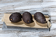 Three avocados (Persea americana) lying on baking paper and slate on wooden table - MAEF007850