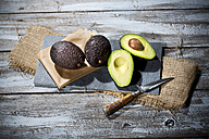 Sliced and whole avocados (Persea americana), baking paper, knife and slate on jute and wooden table - MAEF007819