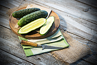 Sliced and whole cucumbers (Cucumis sativus) with knife on chopping board - MAEF007824